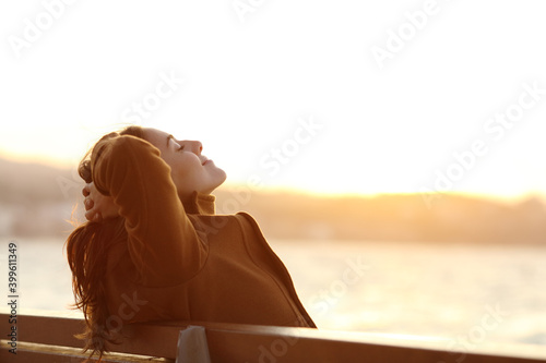 Woman relaxing on a bench in winter on the beach Fototapet