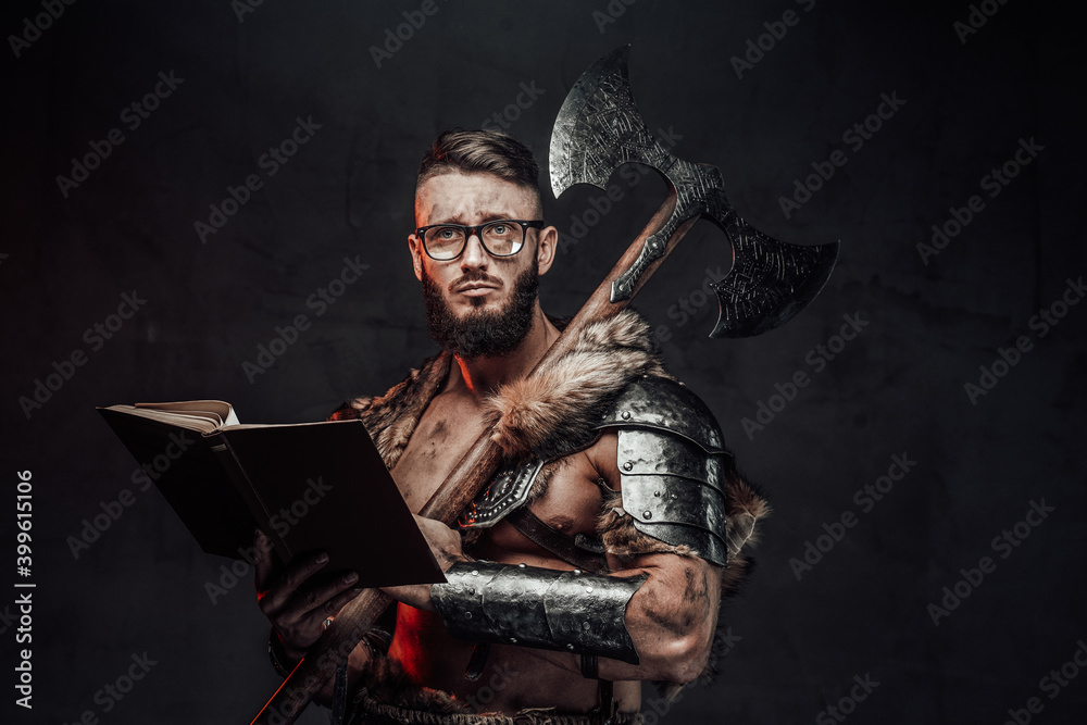 Fototapeta Sad nordic warrior in light armour with fur with eyeglasses and book holding huge axe on his shoulder in dark background.