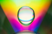 There Is A Large Rainbow-colored Water Drop On The Surface Of The CD.