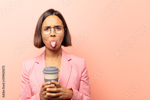 Fotografija young hispanic woman feeling disgusted and irritated, sticking tongue out, disli