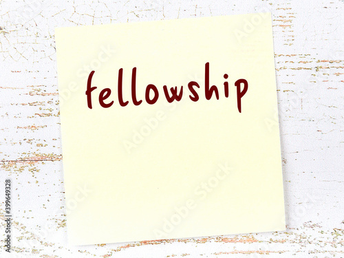 Obraz na plátně Yellow sticky note on wooden wall with handwritten word fellowship
