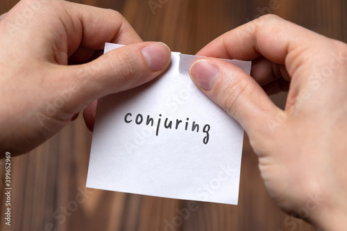 Fotografia Hands of a man tearing a piece of paper with inscription conjuring