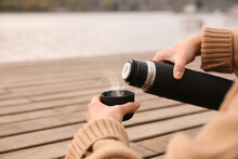 Woman Pouring Drink From Thermos Into Cap At Wooden Table Outdoors, Closeup. Space For Text