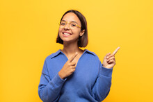 Young Latin Woman Smiling Happily And Pointing To Side And Upwards With Both Hands Showing Object In Copy Space