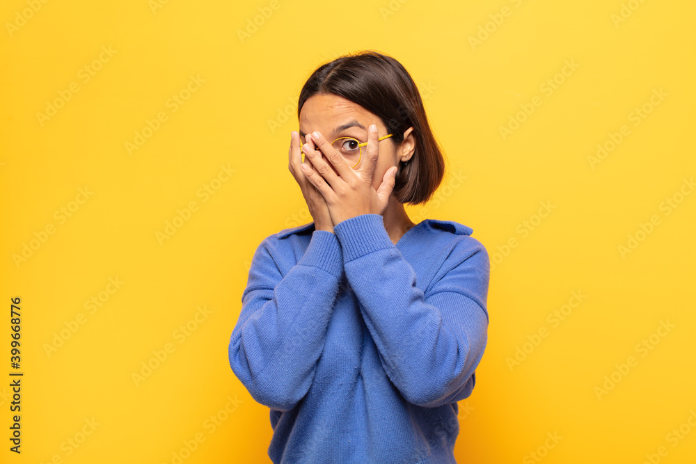 Fototapeta young latin woman feeling scared or embarrassed, peeking or spying with eyes half-covered with hands