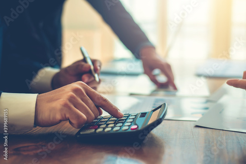 ฺBusinessman using calculator during a business meeting. Fototapet