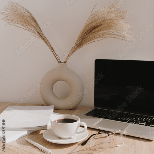 Female home office desk workspace. Blank screen laptop computer with copy space. Coffee cup, pampas grass in stylish vase on beige wooden table. Minimalist lifestyle blog mockup.