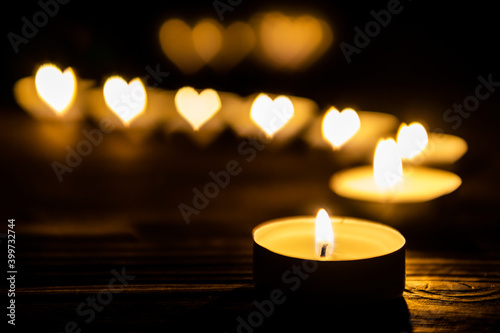 Canvas Print Candles with heart shaped fire are burning in the dark on wooden table