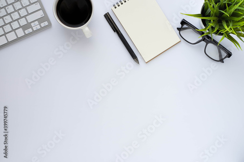 Fototapeta White office desk table with keyboard, notebook and coffee cup with equipment other office supplies. Business and finance concept. Workplace, Flat lay with blank copy space. Top view obraz na płótnie