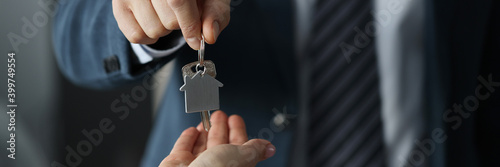 Fotografia Man in business suit hands overing house keys to woman closeup