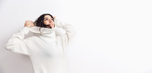 Flyer. Portrait Of Beautiful Brunette Woman In Comfortable Soft Longsleeve Isolated On White Studio Background. Home Comfort, Emotions, Facial Expression, Winter Mood Concept. Copyspace.