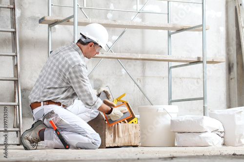Vászonkép plasterer man construction worker takes the plaster trowel from the toolbox wear gloves, hard hat and protection glasses at interior building site with scaffolding