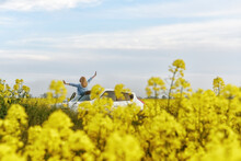 A Girl With Her Hands Raised To The Sky Standing By A Car In A Yellow Flowering Field. Freedom And Travel Concept.
