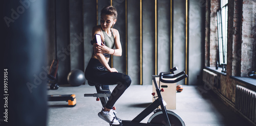 Young sportswoman sitting on cycling machine and fixing smartphone on arm Fototapete