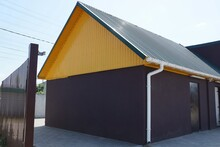 Colored Plastic Building From A Brown Wall With A Yellow Attic Under A Green Roof Against A Blue Sky