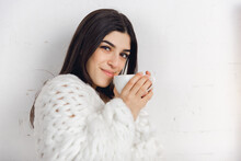 Aroma Tea. Portrait Of Beautiful Brunette Woman In Comfortable Soft Longsleeve Isolated On White Studio Background. Home Comfort, Human Emotions, Facial Expression, Winter Mood Concept. Copyspace.