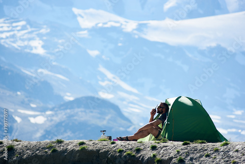 Canvas-taulu Male hiker in sunglasses sitting inside camp tent and using walkie-talkie
