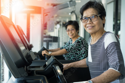 Fototapeta Active Asia senior old women people walk training exercise on treadmill for fit healthy at home gym. obraz