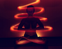 Young Woman Doing Yoga At Night In Her Home In A Moving Flame.