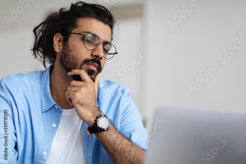 Closeup Portrait Of Focused Handsome Arab Guy In Eyeglasses Working On Laptop Fototapet