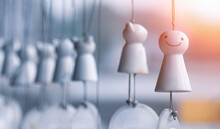 Focus At Japanese Rain Doll On Foreground, Row Of White Ceramic Mobile Hanging With Blurred Background At Morning Time