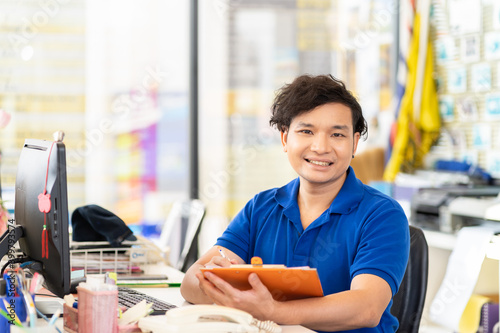 Happy Asian male office worker working at auto car repair shop, sitting while working with computer desktop and clipboard and wearing blue uniform Fototapete