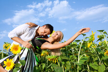 Happy Beautiful Young Couple In A Field Of Sunflowers