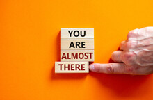 You Are Almost There Symbol. Wooden Blocks Form The Words 'You Are Almost There' On Beautiful Orange Background. Male Hand. Business And You Are Almost There Concept, Copy Space.
