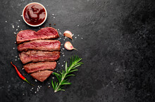 Different Degrees Of Roasting Beef Steak In Heart Shape With Spices On A Stone Background With A Copy Of The Space For Your Text.