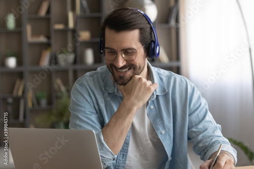 Fototapeta Happy millennial man in headphones and glasses study online or take training on computer on web. Smiling young Caucasian male in earphones work distant on laptop at home office. Technology concept. obraz