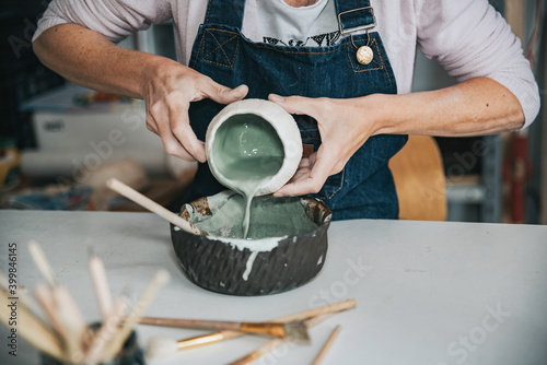 young artisan woman working with her hand a piece of ceramic focus on hand Fototapet