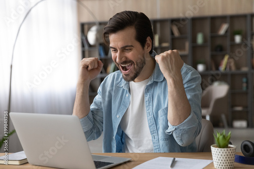 Cuadros en Lienzo Excited young Caucasian man look at laptop screen feel euphoric celebrate online lottery win