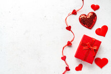 Valentine's Day Composition - Red Gift Box And Decorative, Glitter Hearts On White Stone Background. Flat Lay, Top View, Copy Space. Love Concept.