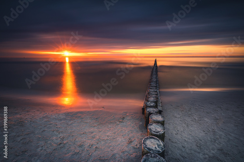 The Baltic breakwaters in Łeba with the setting sun. Long exposure photography.