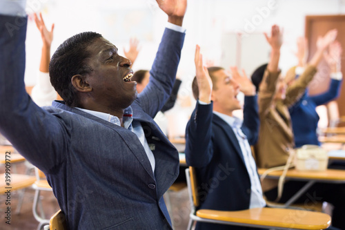 Tela Excited african american man sitting with raised hands during group religious pr