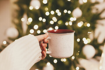 Hand holding festive cup of tea on background of Christmas tree lights bokeh. Merry Christmas and Happy Holidays!