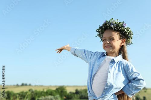 Fototapeta Cute little girl wearing flower wreath outdoors, space for text