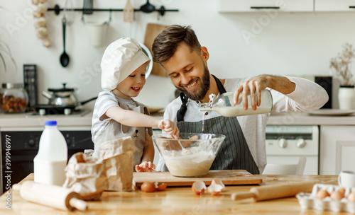 Tela Happy man with kid preparing dough at home.