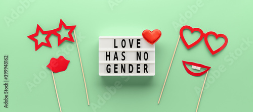 Lightbox with slogan LOVE HAS NO GENDER, red paper props glasses and lips on pastel green ash color background. Concept Homosexuality, lesbian love. Top view, creative flat lay. Holiday Greeting card