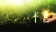 canvas print picture - Hand holding lightbulb and plants with icon wind turbine on soil increase. Concept saving energy in nature, growth and succes. Ecology and Environment conservation concept