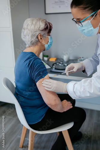 Cuadros en Lienzo Senior woman being vaccinated against coronavirus by a female doctor