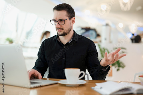 Photo What's wrong Young male freelancer in eyeglasses doesn't understand where is the problem in his code