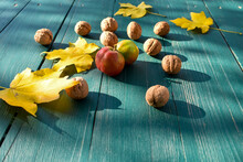 Apple, Fallen Leaves And Ripe Walnuts On The Table