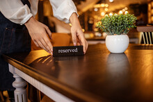 Restaurant Chilling Out Classy Lifestyle Reserved Concept. Waitress Reserving A Tablet At A Restaurant And Putting A Sign On The Table - Food Service Concepts