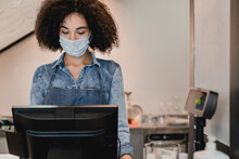Young African Waitress Wearing Medical Mask To Protect From Covid 19 Working At Cash Point In Cafe