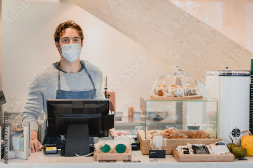 Fototapeta Young handsome caucasian waiter in medical mask against Covid 19 at the cash point in small coffee shop obraz