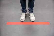 Person Standing Behind Taped Floor Marking Indoors For Social Distance, Closeup. Preventive Measure During Coronavirus Pandemic
