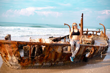 Young Woman Sits On The Hull Of Old Ship. Looks At Nature. The Skeleton Of An Old Destroyed Ship With Rust Is On The Seashore, Damaged During Storm Or  War. Place For Tourists And Photo Session.