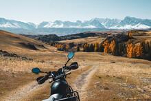 Motorcycle On Dirt Road In Beautiful Mountain Landscape. Orange Autumn, Snow Mountains Peaks Skyline