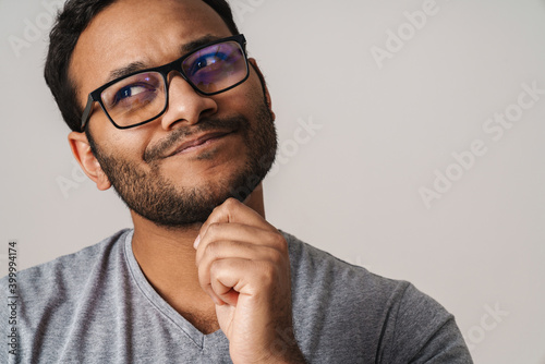 Fotografie, Obraz Asian unshaven man looking at copyspace and touching his chin